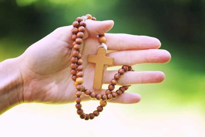 woman hand with wooden rosary
